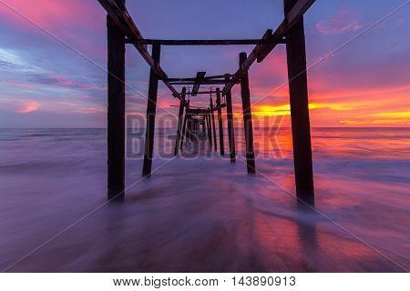 Broken wood bridge and waves crashing on sea at during sunset Phangnga Thailand
