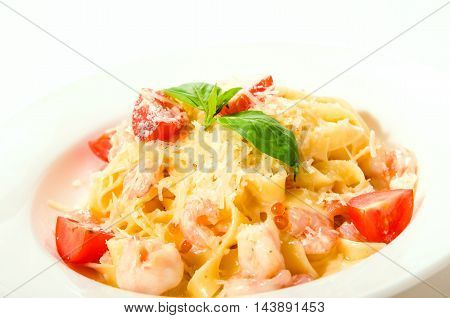 Fettuccine with shrimp tomatoes and pasta noodle on white plate background