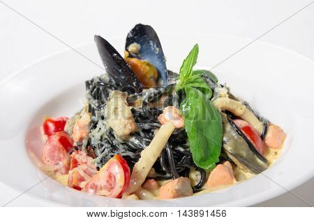 Spaghetti with cuttlefish ink mussels shrimp squid in a creamy sauce with Parmesan