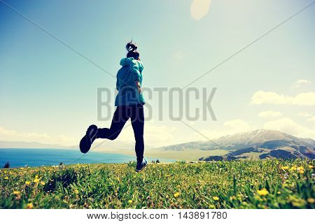 healthy lifestyle young woman trail runner running on beautiful mountain