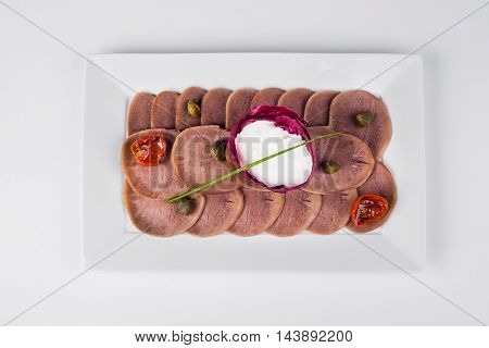 Beef tongue with horseradish and fried tomatoes on white plate background