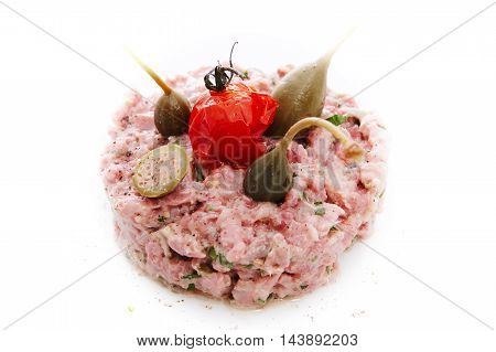 Tartare of cooked beef in its own juice with capers and tuna sauce on white background