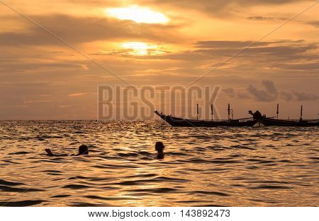 Silhouette of romantic lover swimming in ocean at sunset time koh tao island Suratthani Thailan