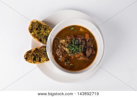 Poucher of Goulash soup with roasted toast and beef on white background