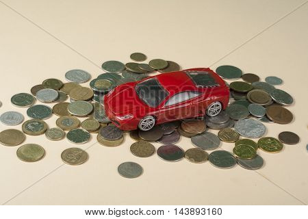 Toy car on coins. Loan, insurance and savings concept.