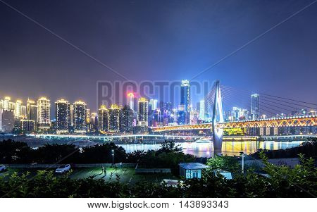 cityscape and skyline of downtown near bridge in chongqing at night