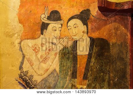 NAN THAILAND - November 24 : Traditional Thai mural painting on temple wall at Wat Phumin on November 24 2013 in Nan Thailand. The famous mural painting of a man whispering to the ear of a woman.