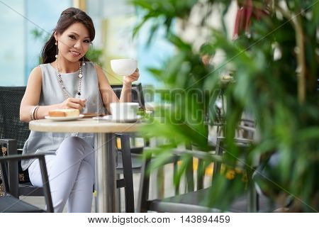 Beautiful young woman drinking cappuccino in cafe