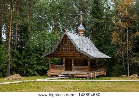 Old orthodox wooden chapel in the forest.