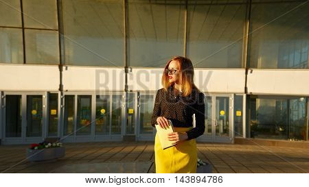 Girl girl in glasses holding hands in the clutch. Business style clothing. Next to the office center. She waiting for a meeting.