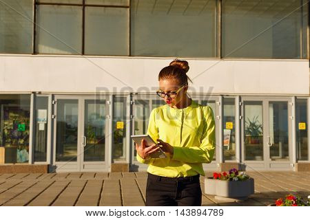 Girl conducts business correspondence in the Tablet PC in the open air. Business woman in glasses. Business style clothing.
