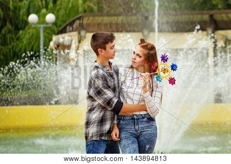 Enamoured teenagers embrace. Girlfriend and boyfriend strolling in a city park. Girl holds in the hands of the pinwheel. A boy in a plaid shirt hugs his girlfriend.