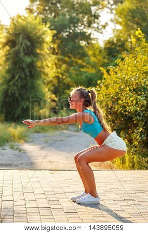 Young slim girl crouching in a city park. Outdoors Sports. Healthy lifestyle concept. Morning exercises .