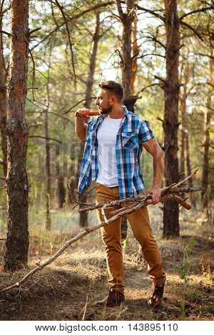 Lumberjack with an ax and firewood. Woodcutter in plaid shirt chopped wood for the fire. Felling trees. Logging. Manual labor.