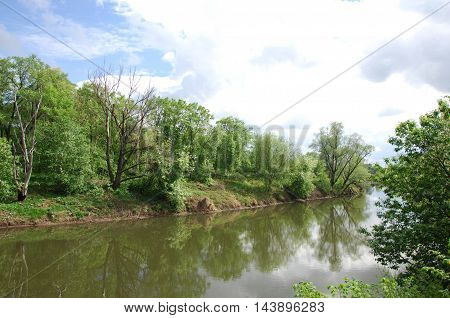 spring river. River and spring forest. Nature composition. Reflexion of clouds in the spring river. Trees on the shore of a river in spring