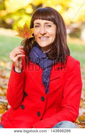 Smiling Woman In Autumn Park With Orange Leaf In Hands