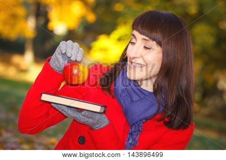 Happy Smiling Woman Holding Book And Apple In Autumn Park