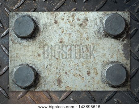 Old and rusty grunge metal plate with rivets on checker plate background
