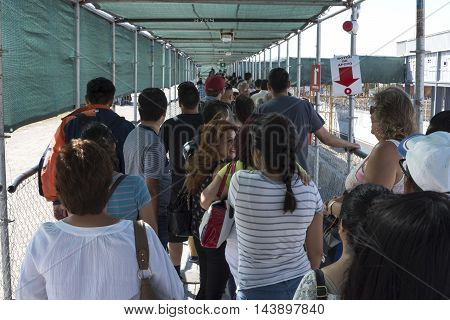 TIJUANA MEXICO - AUGUST 20 2016: Despite the opening of the new PedWest border crossing long waits continue as people stand in line in the temporary corridor leading to the new facility.