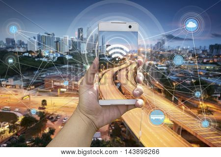 Hand holding white phone with city scape and wifi network connection concept .