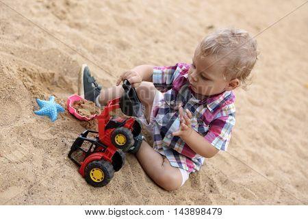 Toddler playing with toy bulldozer in sandbox