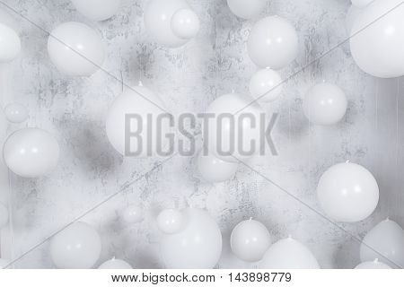 Wgite party balloons infronrt of gray texture wall