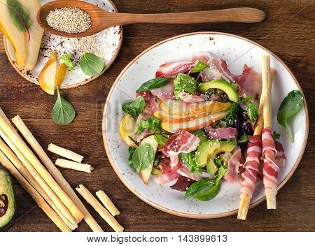 Fresh Mixed Salad With Pancetta And Breadsticks On A Wooden Table.