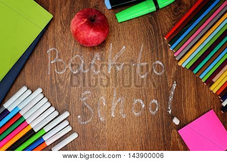 Colored pencils, felt-tip pens and markers, notebooks, stickers  a red apple on the wooden background with the back to school inscription, top view