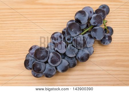 fresh black grapes on a wood table