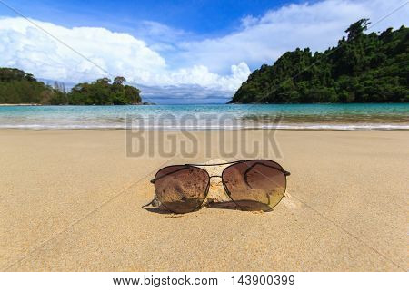 Close up dark glasses on the beach and blue sky background for summer time