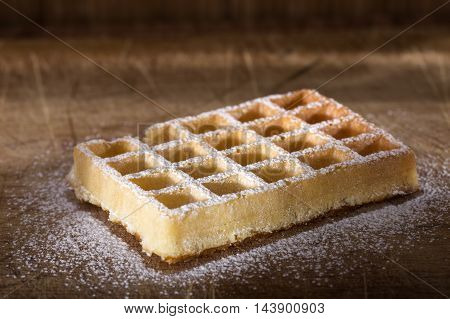 Fresh waffle with powdered sugar on a wooden background