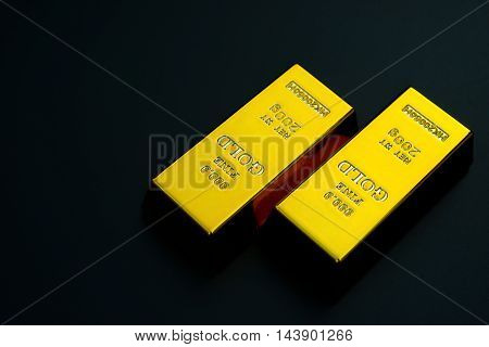two pieces of gold bar on a black background
