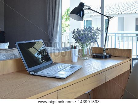 Wooden Table With Computer Notebook,pencil,lamp And Artificial Flowers In Modern Working Area At Hom