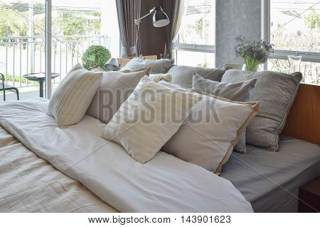 Stylish Bedroom Interior Design With White Striped Pillows On Bed And Decorative Table Lamp.