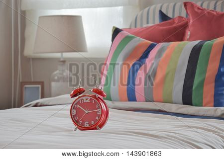 Red Clock On White Blanket And Colourfull Striped Pillows