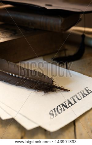 Mortar board and diploma text signature on a wooden table