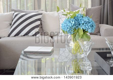 Light Blue Flower And Wine Glasses On Center Table With Striped Black And White Pillow And Gray Tone