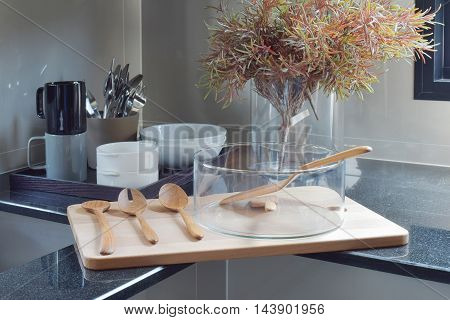 Glass bowl with wooden utensil on wooden tray in the kitchen