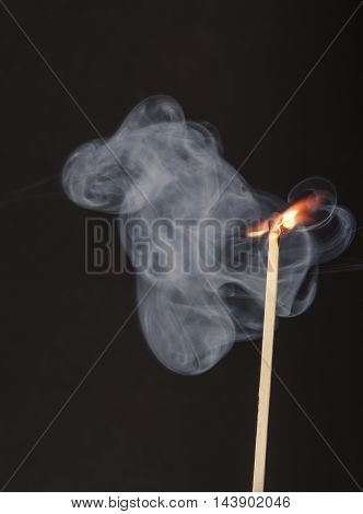 Large Match Igniting From Heat Of Candle Flame Showing Smoke Trails And Explosion