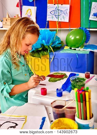 Close up of little child girl painting picture on desk in primary school. In primary school lot of child picture in kindergarden.