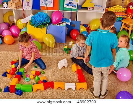 Large group children game blocks on floor in primary school. Top view. Children plays together in primary school. Children play on a soft carpet.
