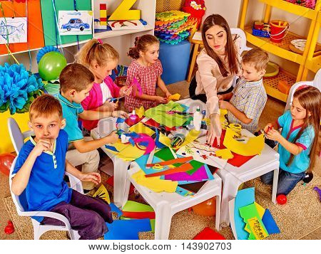 Large group of children with teacher are making something out of colored paper on table in primary school. Childrens crafts out of paper. Top view of primary school.