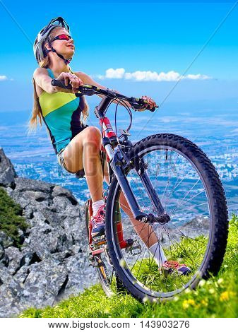 Girl rides bicycle aganist blue sky . Girl in cycling. Located at bottom of city. Bicyclist pulls into steep hill.