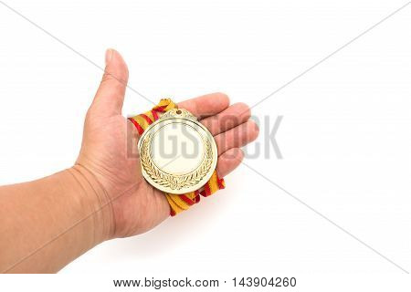gold medal on males hand on a white background