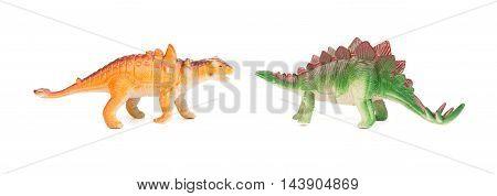 green stegosaurus and orange pinacosaurus toy on a white background