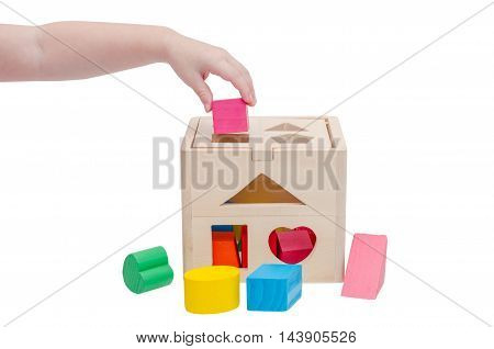 Child's hand putting wooden toy shape into wood box over white background
