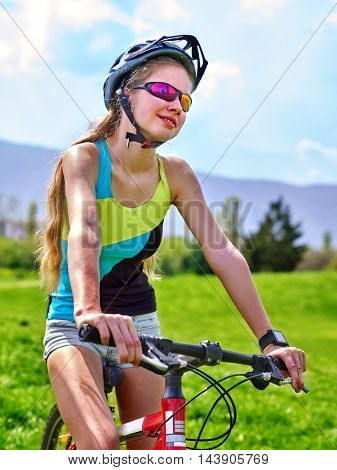Girl rides bicycle aganist blue sky . Girl in cycling. Cyclist looking up on blue sky. Bicycle girl wearing T-shirt and bicycle shorts