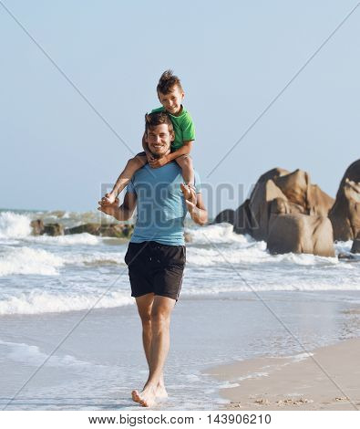 happy family on beach playing, father with son walking sea coast, rocks behind smiling