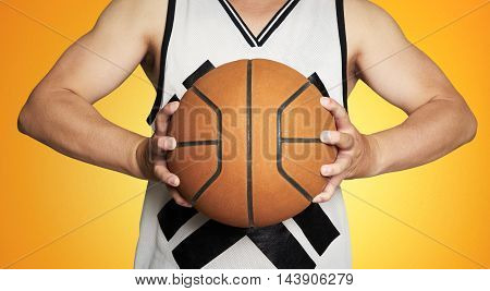 Close up of young man midsection holding a basketball