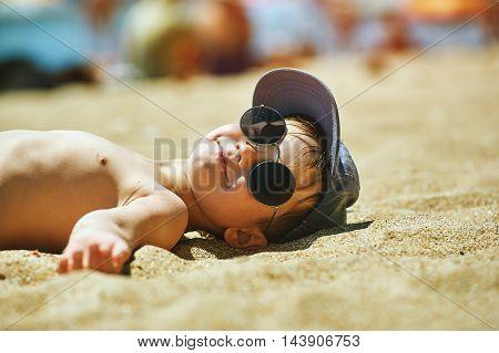 happy boy on the beach , sunglasses . Summer vacation